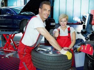 Two motor mechanics fitting a summer tyre